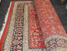 Oriental rug partially rolled up on the floor.