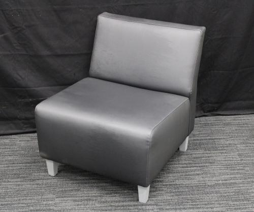 Grey chair against a black backdrop.